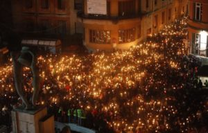 People take part in a torchlight procession for earthquake victims in L'Aquila